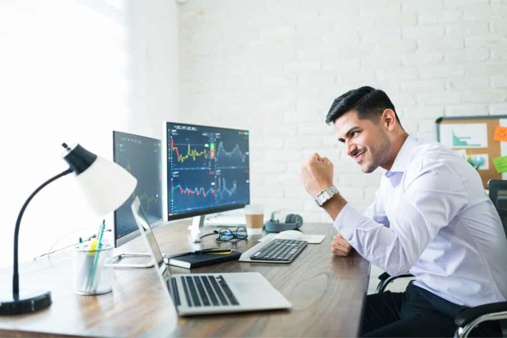 day trading and swing trading traders. Happy trader in front of computer with currency charts