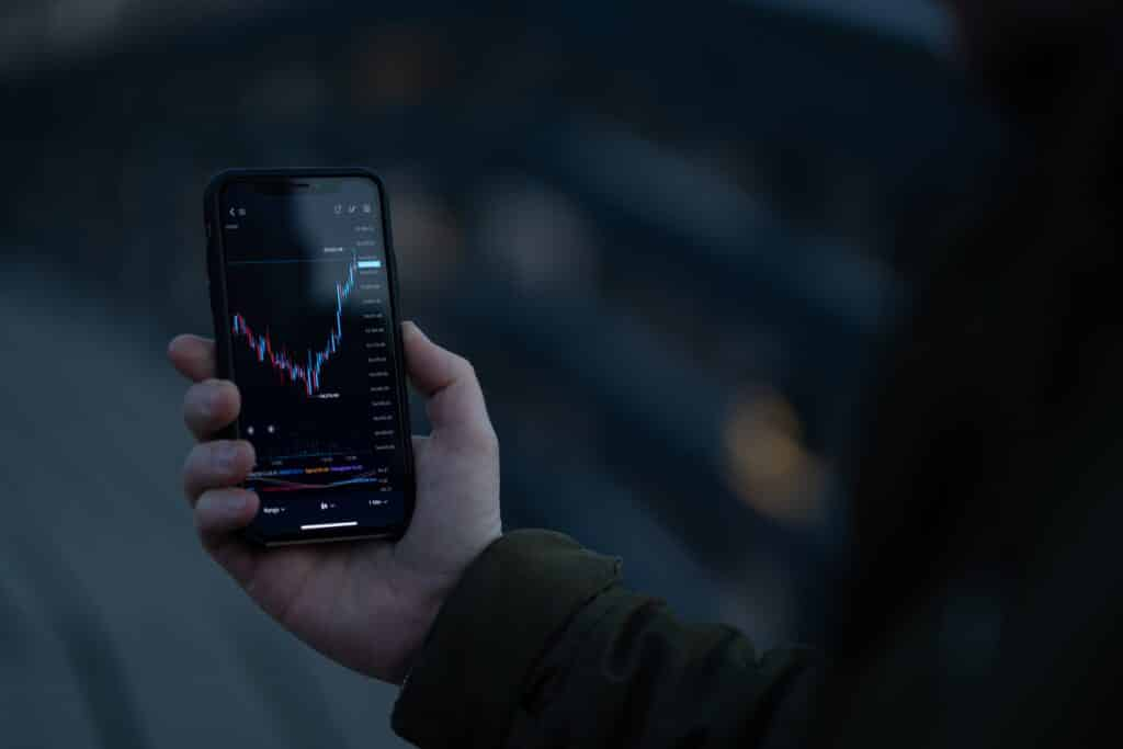 Male investor using stock trading app on smartphone, trader analyzing dynamic on forex chart and price flow on screen while standing outdoors. Selective focus on hand holding mobile phone on MT4