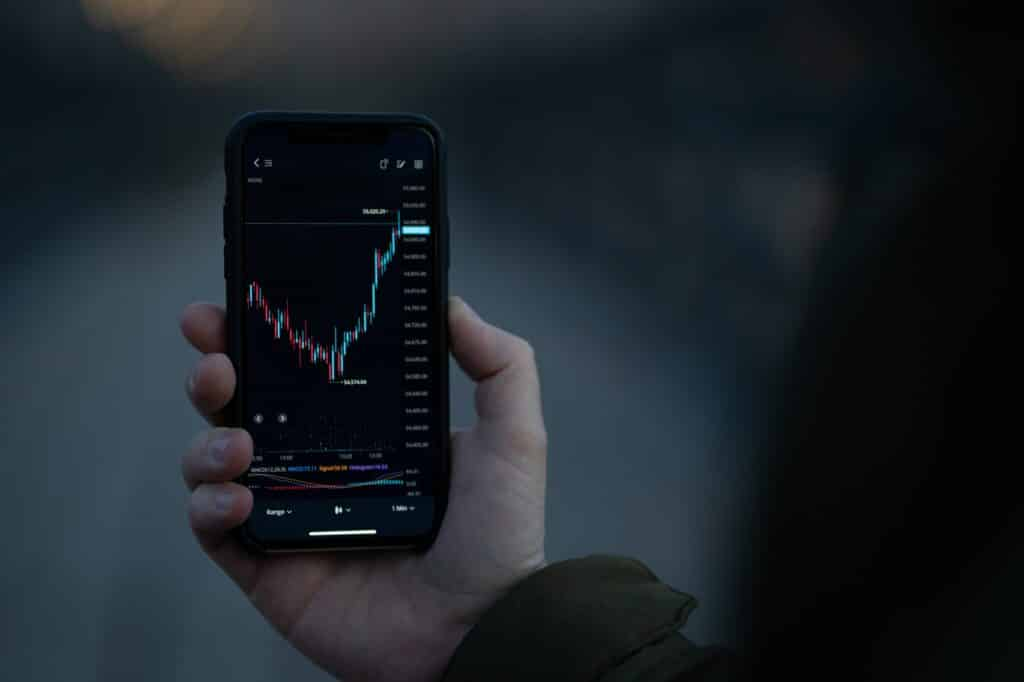 Male hand holding smartphone with real time forex chart on screen