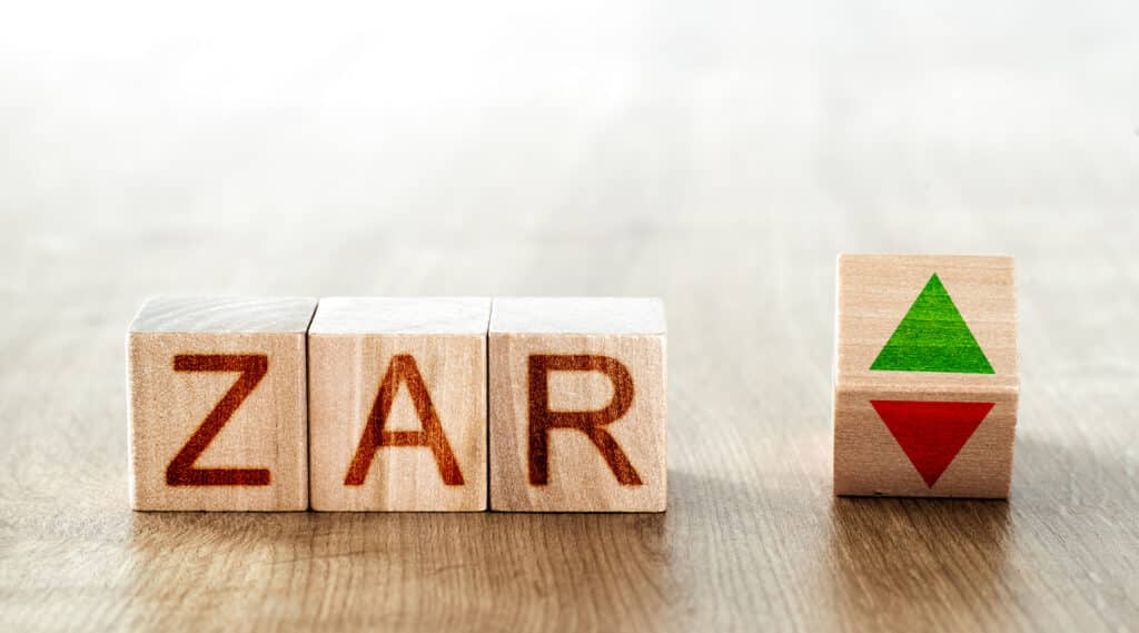 wooden blocks with the inscription zar and a block symbolizing the rise and fall of financial markets
